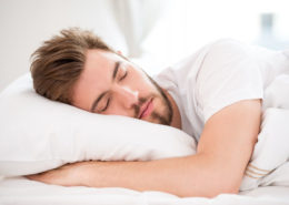 32122504 - handsome young man with a beard sleeping in white bed